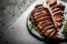 Barbecue Aged Wagyu Porterhouse Steak Sliced As Top View On A Slate Board, Beef T-Bone Juicy Steak Rare Beef With Spices On A Black Table, Banner, Catering Menu Recipe Place For Text, Top View