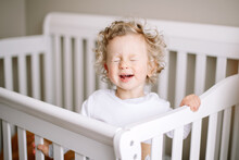 Cute Adorable Baby Boy Crying In Crib At Kids Nursery Room At Home. Funny Baby Boy With Curly Blond Hair Screaming At His Bed. Terrible Two Toddler Childhood Crisis. Authentic Candid Home Life.