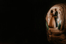 Couple Bride And Groom Wedding Dress Stand In A Hole In Rock. Monastery Bakota. Natural Tunnels Rocks Of Ukraine