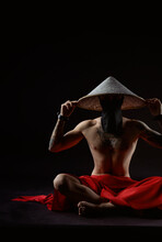 A Slender Samurai In A Red Raincoat And An Asian Hat Sits In The Lotus Position