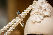Artistic Photo Of Deep Blue Wedding Diamond Ring On A String Of Pearls With Blurred Background. Modern Style.
