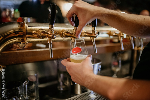 Tela Selective focus shot of a person pumping beer from a cask of a beer engine