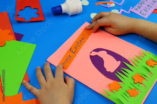 Obraz child makes a gift card for Easter from colored paper - fototapety do salonu