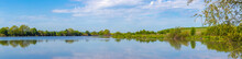 Wide Panorama With River And Trees Reflected In The Water