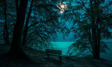 View At Night From The Chalk Cliffs On The Island Of Ruegen To The Baltic Sea. The Full Moon Is In The Sky Over The Sea. In The Foreground Is A Bench In The Moonlight.