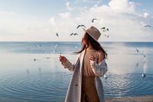 Beautiful Asian Woman Poses With Seagulls Near Sea.