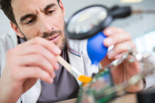 Man Working Carefully With Paint Brush Under Magnifying Glass