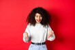 Leinwandbild Motiv Dreamy beautiful woman with curly hair, pointing and looking down excited, checking out promo, standing against red background