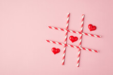Happy Saint Valentines Day Concept. Above Overhead Flat Lay View Photo Of Crossing Straws And Small Hearts Making A Line Isolated Light Background With Empty Space