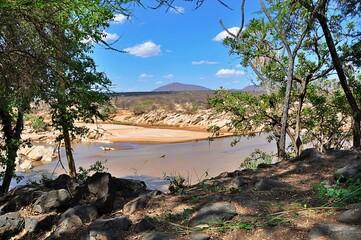 Widok z pomiędzy drzew na rzekę i step. Rezerwat Shaba (Kenia)