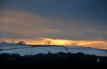 Glowing Orange Sunset In A Cloudy Twilight Winter Sky With Snow Covered Fields With Stoodley Pike Monument In The Distance In Calderdale West Yorkshire