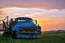An Old Chevy Truck In Front Of A Colorful Sunset