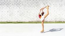 Teenage Girl Practicing Figure Skating On Four Wheels. Exercise The Basket Or Diamond