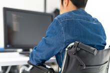 パソコンを使う男性身体障害者・車椅子