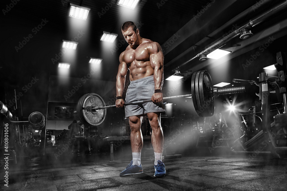 Fototapeta Athlete muscular brutal bodybuilder training workout with heavy barbell in the gym