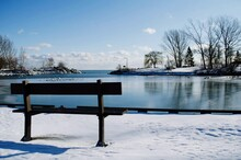 Empty Bench By Frozen Lake Against Sky During Winter
