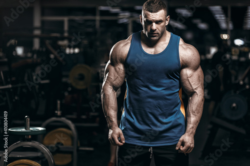 Obraz Muscular man bodybuilder training in gym and posing. Fit muscle guy workout with weights and barbell  - fototapety do salonu