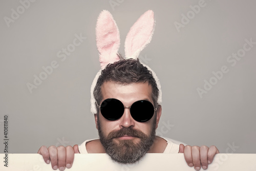 Funny man with beard in bunny ears and glasses on serious face with paper on gre Fototapeta