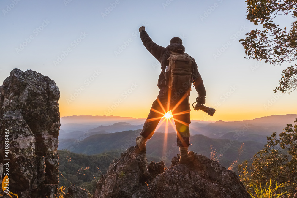 Fototapeta Professional photographer holding camera on the peak of rocks mountain with stretching hands at sunset, success,winner concept