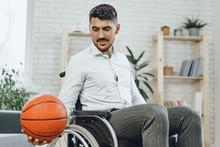 Disabled Young Man In Wheelchair Holding Basketball Ball