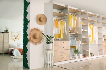 Big wardrobe with different clothes and accessories in studio apartment