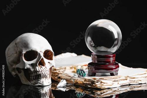 Photo Crystal ball of fortune teller, human skull and old book on dark background