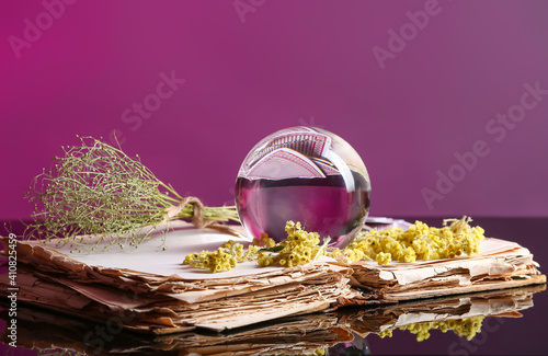 Photo Crystal ball of fortune teller, old book and dry herbs on table