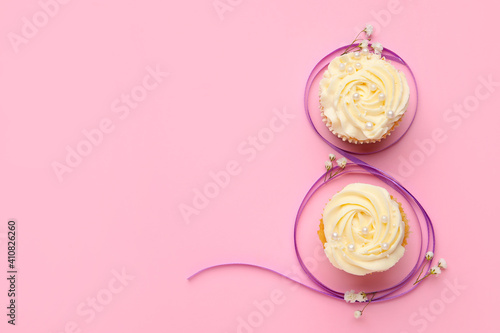 Fotografie, Obraz Figure 8 made of violet ribbon and cupcakes on color background