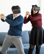 Portrait Of Cute Smiling Young Asian Lover Couple Having Fun With Playing A New Video Game With Virtual Reality Headset Glasses Together Like Fighting Or Sports Game. New Digital Trending VR Concept