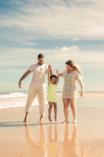 Happy Family Couple And Little Girl Enjoying Walking And Activities On Beach, Kid Holding Parents Hands, Jumping And Hanging. Front View. Family Outdoor Activities Concept