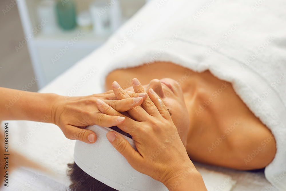 Fototapeta Woman getting professional face lifting massage while relaxing in modern spa salon