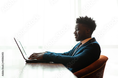 Obraz handsome young african man in suit indoors with laptop  - fototapety do salonu