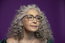 Studio Portrait Of A Smiling Elderly Woman 60-65 Years Old With Glasses, With Gray Curly Long Hair, On A Colored Background, Concept: Stylish Pensioners Of Model Appearance, Active Life,