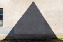 Shadow Of A Peaked Roof On A Light Roughcast Wall Of A House Next To A Window With Glass Blocks That Have Different Dark Colors