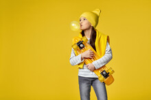 Cool Hipster Little Child Girl With Yellow Skateboard Blowing A Big Bubble Gum Over Yellow Background. Copy Space