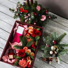 A Burgundy Wooden Box Lies On A Gray Wooden Board Inside Which Lies Red Roses With Parts Of The Foliage Of A Christmas Tree With A Pink Perfume Box And A Glass Jar