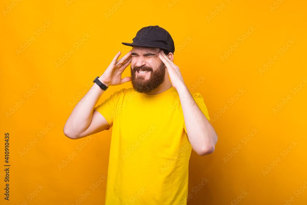 Fototapeta Photo of young man having headache over yellow background.