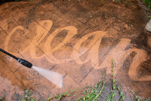 Cleaning Backyard Paving Tiles With Pressure Washer.