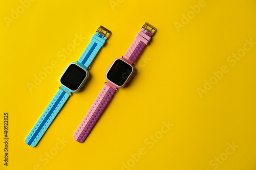 Fototapeta Kid smart watches on yellow background, flat lay. Space for text obraz