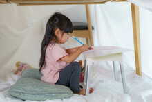 Asian Cute Little Girl Drawing In Paper While Lying In A Blanket Fort In Living Room At Home For Perfect Hideout Away From Their Other Family Members And For Them To Play Imaginatively.