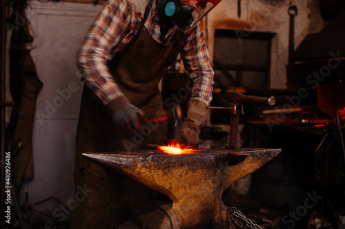 The blacksmith manually forging the molten metal on the anvil in smithy with spark fireworks Poster Mural XXL