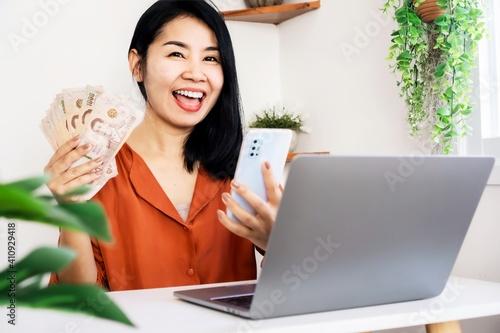 Fényképezés happy Asian woman successful make money online hand holding Thai baht money and