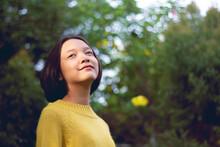 Smiling Teenage Girl Looking Away Against Trees In Park