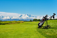 Golf Cart With Bag And Golf Clubs At The Edge Of The Fairway Of A Golf Course. In The Background The Alps, The Monte Rosa Chain, Seen From The Italian Side.