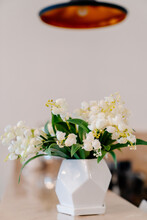 Small White Vase With Lilies Of Valley On Table Under Black Copper Chandelier.