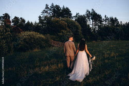 Fototapety, obrazy: Walk the newlyweds at sunset. The bride and groom in the rays. Evening landscape.