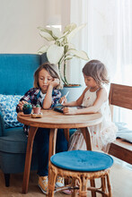 Two Smart Children Sit At Table Together And Paint On Tablet With A Digital Pencil In Modern Living Room.