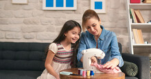 A Young Woman And Her Daughter Sew Clothes With A Sewing Machine On The Sofa. The Woman And Her Daughter Spend Time Together, Smile And Enjoy Creative Work.