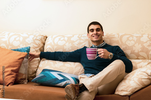 cheerful young man drinks coffee on the sofa at home in the morning before going to work