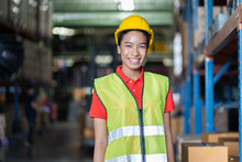 Portrait Of Smiling Black Female Warehouse Worker At Work In The Industry Storage Warehouse. African American Woman In Safety Vest And Helmet At The Shelves Shelf Warehouse